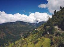 Terrassen in den Bergen mit Wolken und Annapurna Süd lizenzfreie stockbilder
