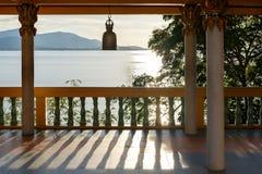 Terrassera med kolonner, den buddistiska klockan, sikten av havet och berg i avståndet Fotografering för Bildbyråer