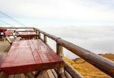 Terrassera med tabeller och träbänkar på bergtoppmöte oklarhet Arkivfoto