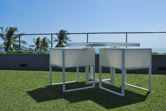 Terraszitkamer met witte rotanleunstoelen Stock Foto's