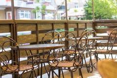 Terraza acogedora del café del verano con las tablas y las sillas de mimbre Foto de archivo libre de regalías