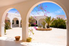 Terraza al aire libre con las flores rosadas de la buganvilla, museo de Djerba, Túnez fotos de archivo