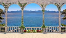 Terraza con la barandilla que pasa por alto el mar y las montañas Foto de archivo