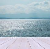 Terraza de madera en la playa con el cielo claro, Crystal Clean y las ondas claras del mar y grandes viniendo al fondo del paisaj Foto de archivo libre de regalías