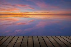 Terraza de madera y la reflexión de la puesta del sol Fotos de archivo libres de regalías