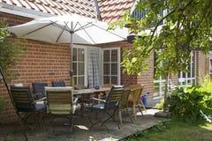 Terraza del verano en la casa con la tabla y muchas sillas bajo s Imagen de archivo