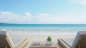 Terraza y camas en casa de playa de lujo moderna con el fondo del cielo azul, sillones de la opinión del mar en cubierta de mader