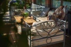 Terrazzo accogliente con i sofà per resto, vetro con champagne su una tavola di legno Immagine Stock Libera da Diritti