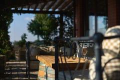 Terrazzo accogliente con i sofà per resto, vetro con champagne su una tavola di legno Fotografie Stock Libere da Diritti