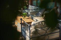 Terrazzo accogliente con i sofà per resto, vetro con champagne su una tavola di legno Immagine Stock