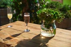 Terrazzo accogliente, vetro con champagne su una tavola di legno Immagine Stock Libera da Diritti