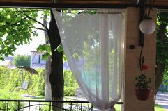Terrazzo del ristorante di estate o interno della veranda con spazio aperto Vista della decorazione e del giardino dell'erba fotografie stock