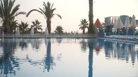 Terrazzo di rilassamento vicino alla piscina di lusso della località di soggiorno operata e di belle palme al tramonto video d archivio
