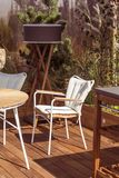 Terrazzo lussuoso con mobilia moderna e progettazione naturale Sedia bianca sul pavimento di legno e sulle belle piante fotografie stock libere da diritti