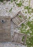 Terrazzo, tavola e sedie da legno grigio sulle pietre fotografia stock