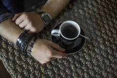 Terrazzo tipico del caffè con la tazza di coffe sulle mani del ` s dell'uomo e della tavola immagine stock libera da diritti