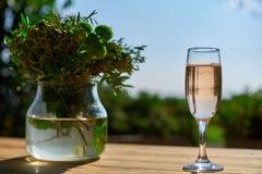 Terrazzo, vetro con champagne su una tavola di legno Immagini Stock Libere da Diritti