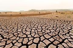 Terre sèche criquée sans eau abrégez le fond images stock
