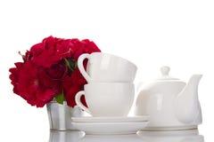 Terrecotte bianche per tè e un mazzo delle rose Fotografie Stock
