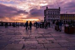 Terreiro do Paço, Lissabon - Maart 17, 2019 - Mensen die in het vierkant onder een verblindende en kleurrijke zonsondergang, Por stock afbeeldingen