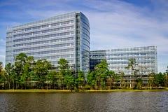 Terreni boscosi del lago ed edifici per uffici Fotografia Stock