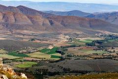 Terreni coltivabili con le montagne nella priorità alta Fotografia Stock