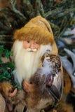 Terreno boscoso Santa con un gufo sul suo braccio davanti ad un albero di Natale immagini stock libere da diritti