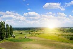 Terreno collinoso, giacimento della molla ed alba su cielo blu Fotografie Stock Libere da Diritti