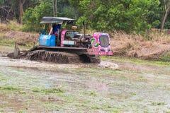Terreno coltivabile di agricoltura, trattore con l'aratro che ara un campo del suolo Fotografie Stock
