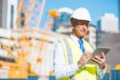 Terreno de construção do gerente da construção e dispositivo de controlo da tabuleta em suas mãos imagem de stock royalty free