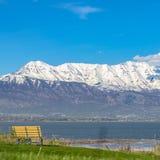 Terreno gramíneo do quadrado com um banco exterior vazio que enfrenta um lago e uma montanha nevado fotos de stock