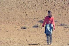 Terreno incolto d'escursione femminile sportivo del deserto attraverso il cratere vulcanico immagini stock