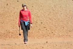 Terreno incolto d'escursione femminile sportivo del deserto attraverso il cratere vulcanico immagine stock