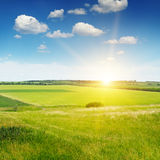 Terreno montanhoso, campo da mola e nascer do sol no céu azul imagens de stock