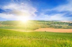 Terreno montanhoso, campo da mola e nascer do sol no céu azul fotografia de stock royalty free