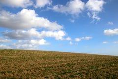 Terreno montanhoso com céu azul e nuvens fotografia de stock