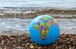 Terrestrial globe on a marine beach Stock Images
