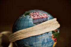 Terrestrial globe with a piece of cloth tied around it Royalty Free Stock Photography