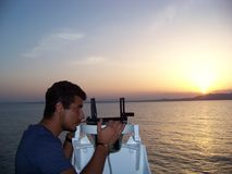 Terrestrial navigation with pelorus and landmarks to find out position at anchorage. Trainee is appointing the position of the vessel at anchorage during sunset Stock Photos