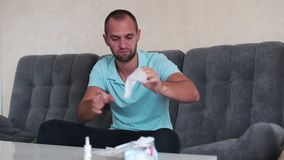 Terrible allergy. Frustrated handsome young man sneezing and using tissue while sitting on the couch at home stock footage