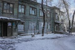 A terrible apartment house. The old wooden barrack, the windows are covered with cellophane tape. Poor living conditions. Around snow, winter frosty day Stock Photography