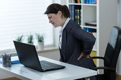 Terrible backache. Young woman with sitting job having terrible backache Royalty Free Stock Photography
