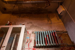 Terrible bloodied battery near glass case in dimly lit basement. With pipes and wires in foreground in a Halloween horror concept Royalty Free Stock Image