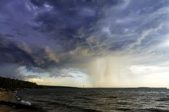 A terrible blue cloud with a heavy rainfall over the sea. stock images