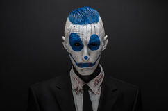 Terrible clown and Halloween theme: Crazy blue clown in black suit isolated on a dark background in the studio. Terrible clown and Halloween theme: Crazy blue Stock Photography