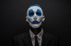 Terrible clown and Halloween theme: Crazy blue clown in black suit isolated on a dark background in the studio. Terrible clown and Halloween theme: Crazy blue royalty free stock image
