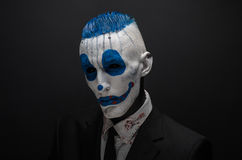 Terrible clown and Halloween theme: Crazy blue clown in black suit isolated on a dark background in the studio Royalty Free Stock Images