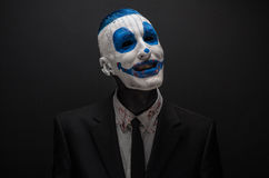 Terrible clown and Halloween theme: Crazy blue clown in black suit isolated on a dark background in the studio Royalty Free Stock Photos