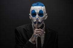 Terrible clown and Halloween theme: Crazy blue clown in black suit isolated on a dark background in the studio. Terrible clown and Halloween theme: Crazy blue stock photo