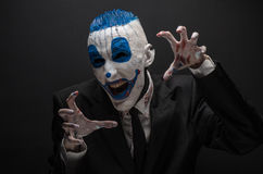 Terrible clown and Halloween theme: Crazy blue clown in black suit isolated on a dark background in the studio Royalty Free Stock Image